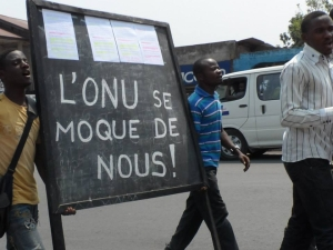 "The board that these Congolese protesters in Goma - Eastern Congo reads ""UN is mocking us."" For Congolese people it  is time to end that mockery by demanding immediate removal of MONUSCO. As the situation evolves presently, it appears that Congolese population national uprising against UN presence and Kabila government in Kinshasa might start in the Kivu provinces."